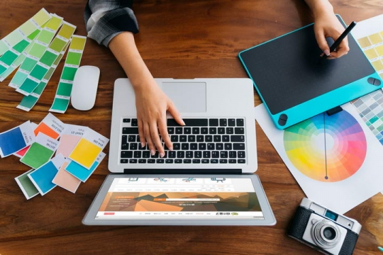 俯视视角的设计师正在操作苹果笔记本电脑MacBook屏幕显示样机