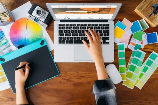 俯视视角平面设计师利用苹果笔记本电脑MacBook和绘图板正在工作样机图片