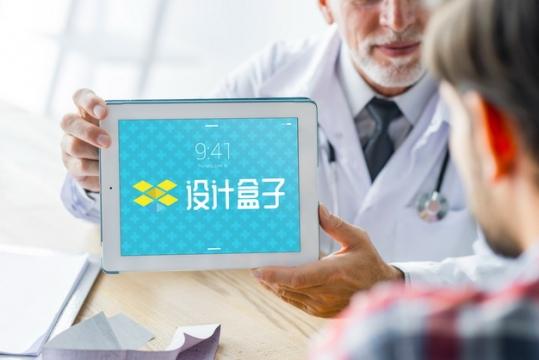 医生拿着平板电脑向病人展示psd样机图片模板素材